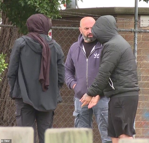 A group of men gathered in the suburban street as a woman spoke to someone over the phone